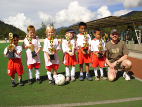 A Redpath employee poses with our sponsored children's soccer team in Indonesia.