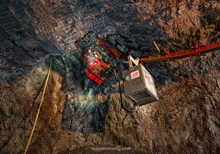 An employee operates raisemining equipment in an underground mine.