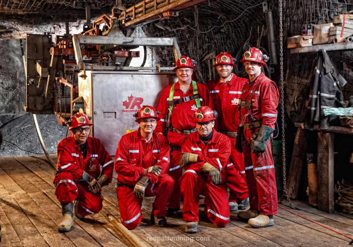 A group of employees poses in an underground mine.