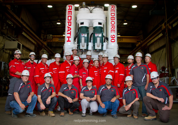 A group of employees poses in front of the Redbore 90.