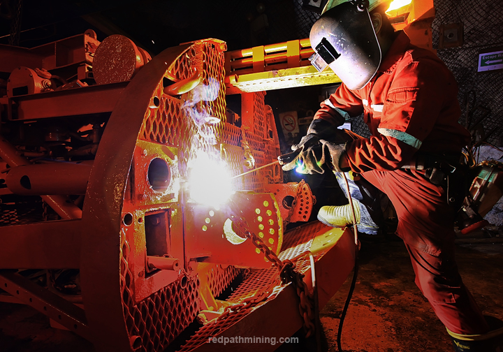 An employee welds a piece of equipment in an underground mine.