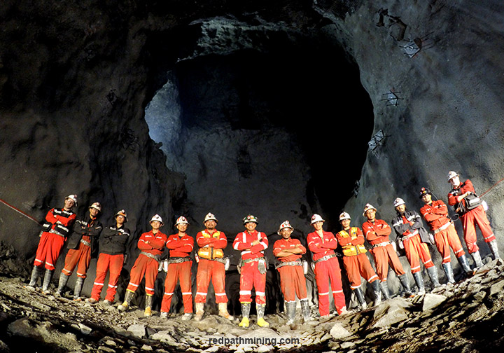 A group of employees poses in an underground mine in Asia.