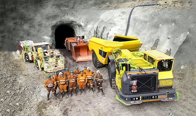 Employees pose with equipment at the portal of a mine site in Australia.