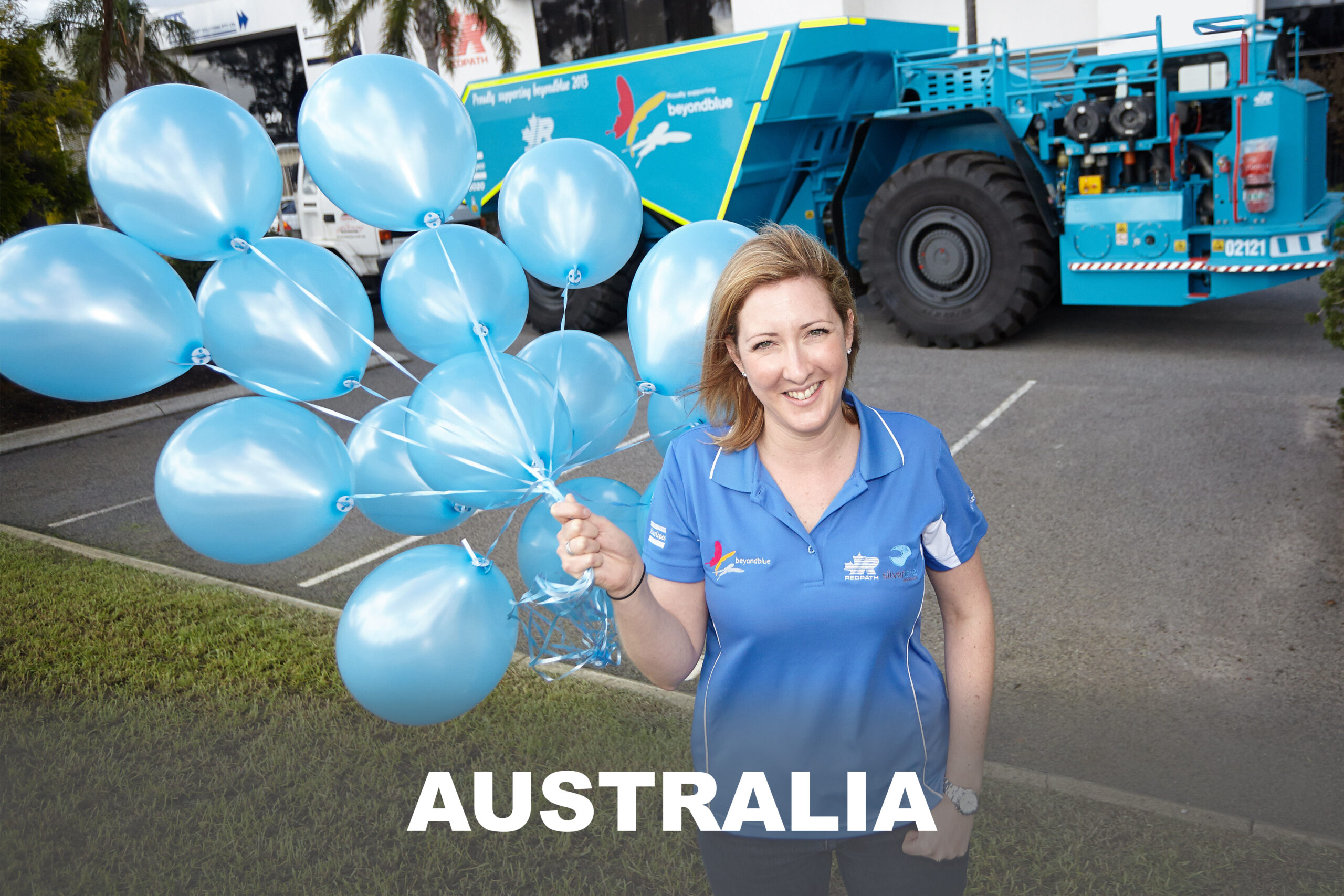 A Redpath Australia employee poses in front of the office with